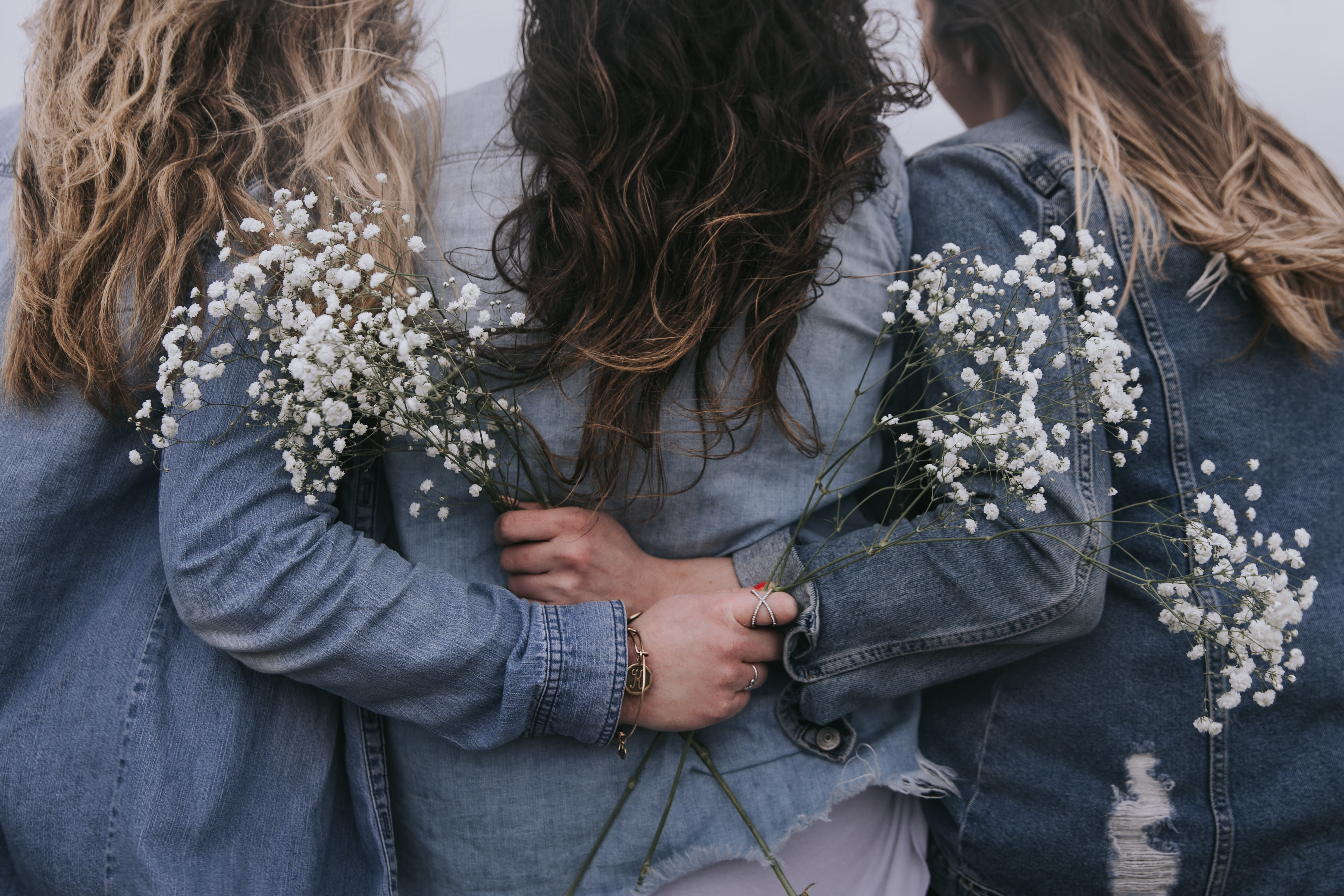 Three women holding each other, all wearing denim jackets.