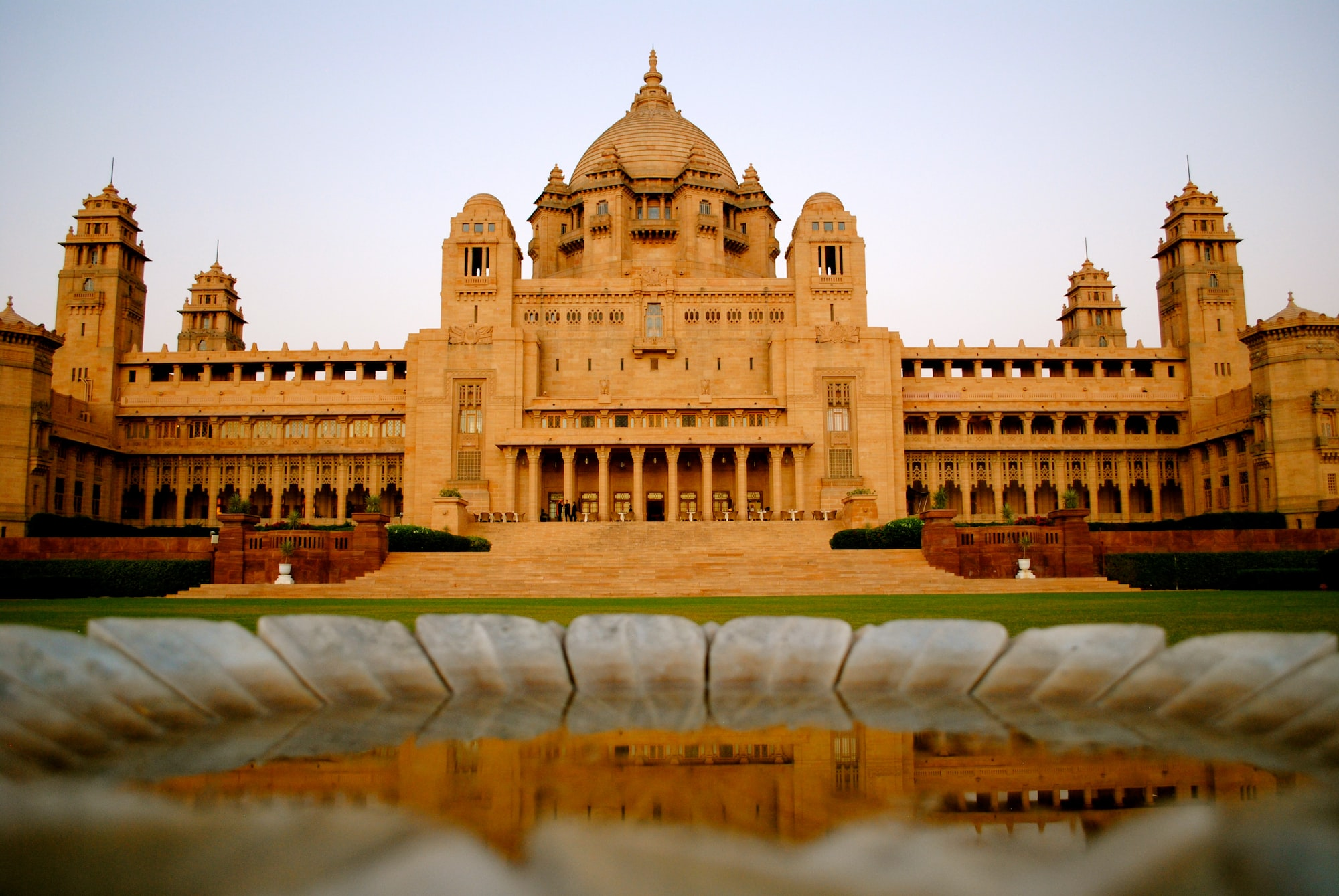 This picture was taken just before sunset , with me lying prostrate on the ground and I had used the edge of the marble bowl as an alternative to a  tripod and then taken it. The magnitude of the Umaid Bhavan palace  and it's reflection in the water captured the whole ambience, is what I thought !