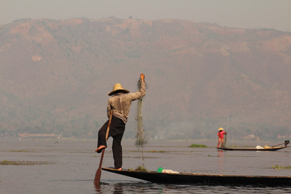 man standing on boat and fishing