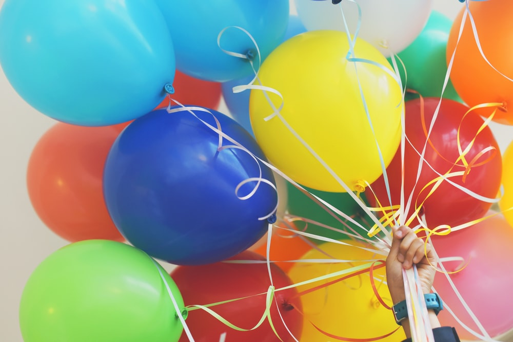 A person holding up a bunch of colorful balloons.