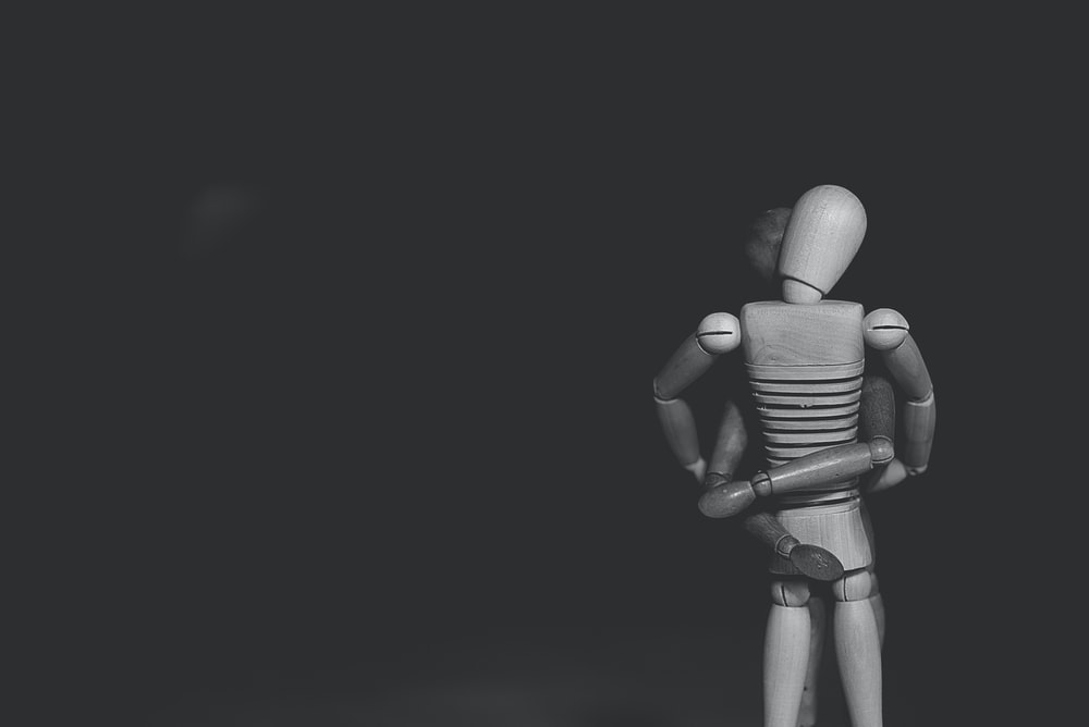 grayscale photo of joint action figure hugging one another