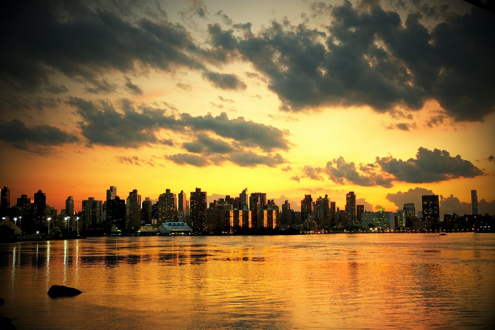 photo of cityscape under white clouds during golden hours