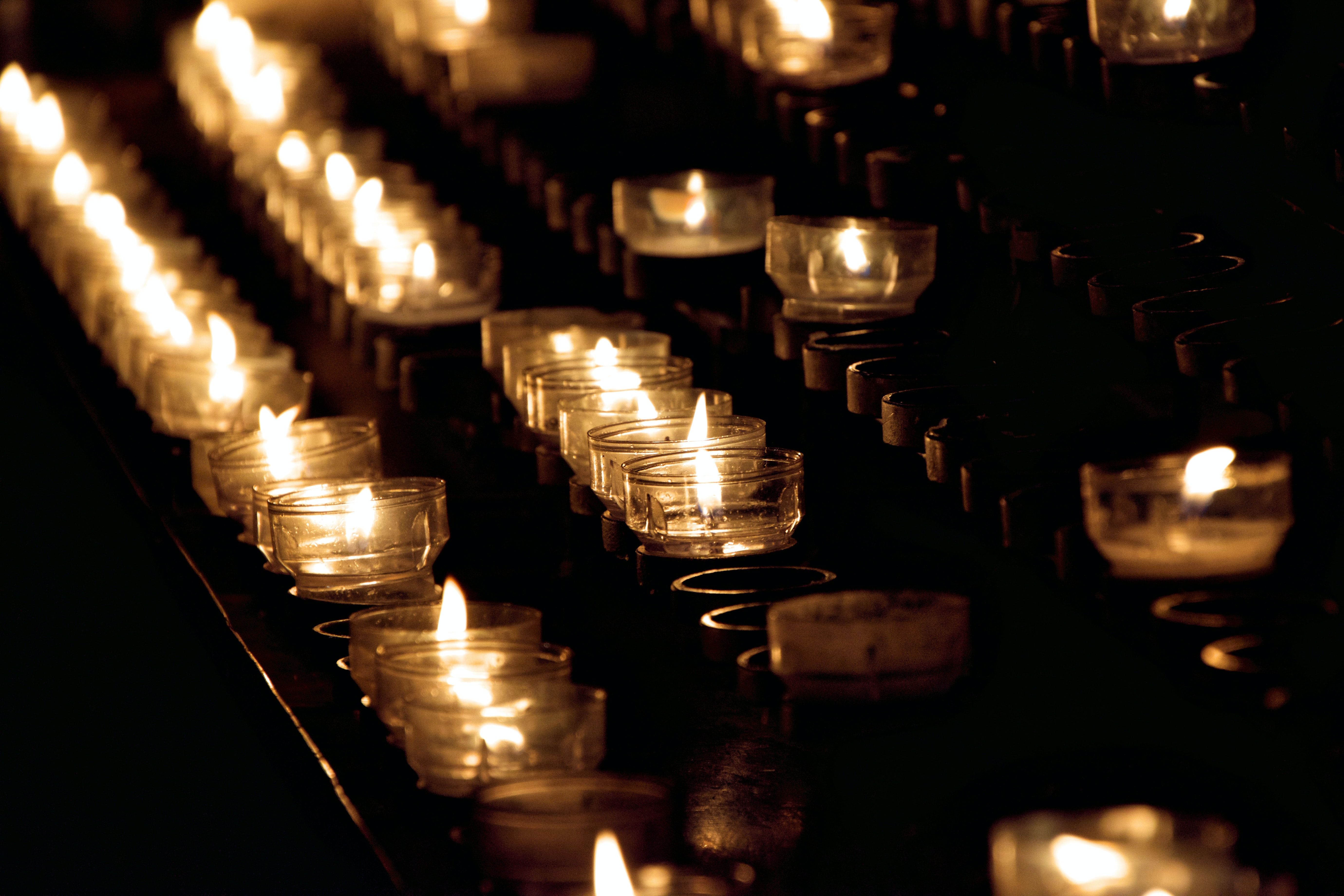 closeup photo of lighted tealight candles on rack