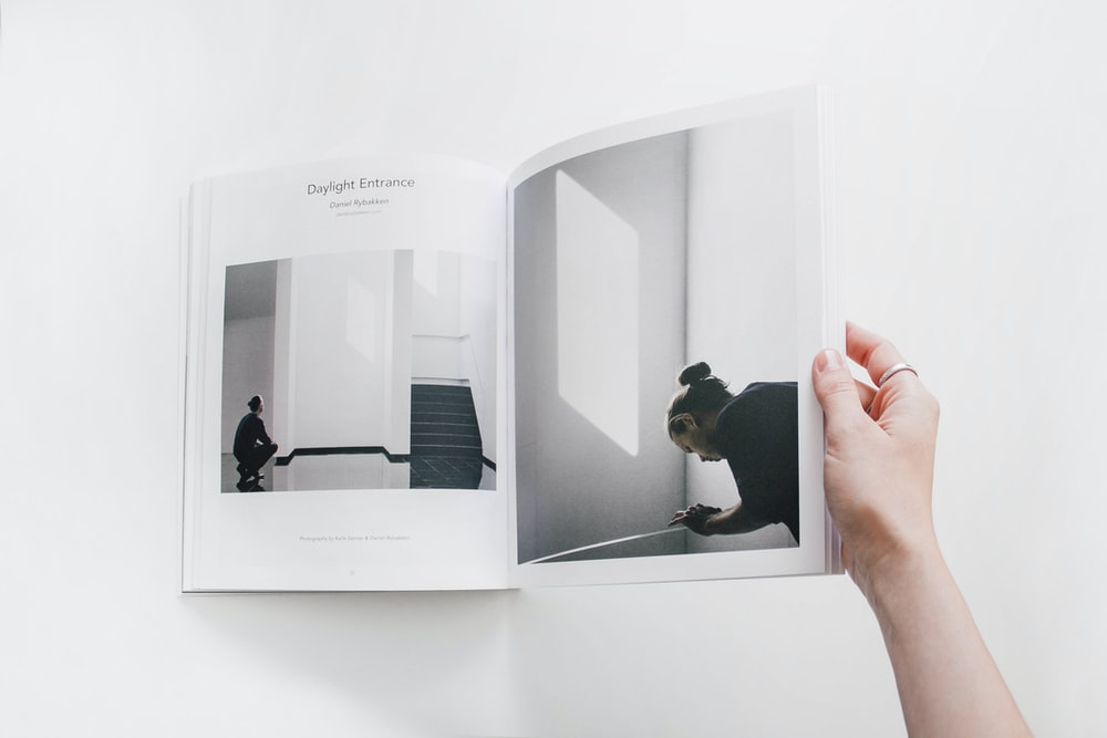 person reading book on white surface