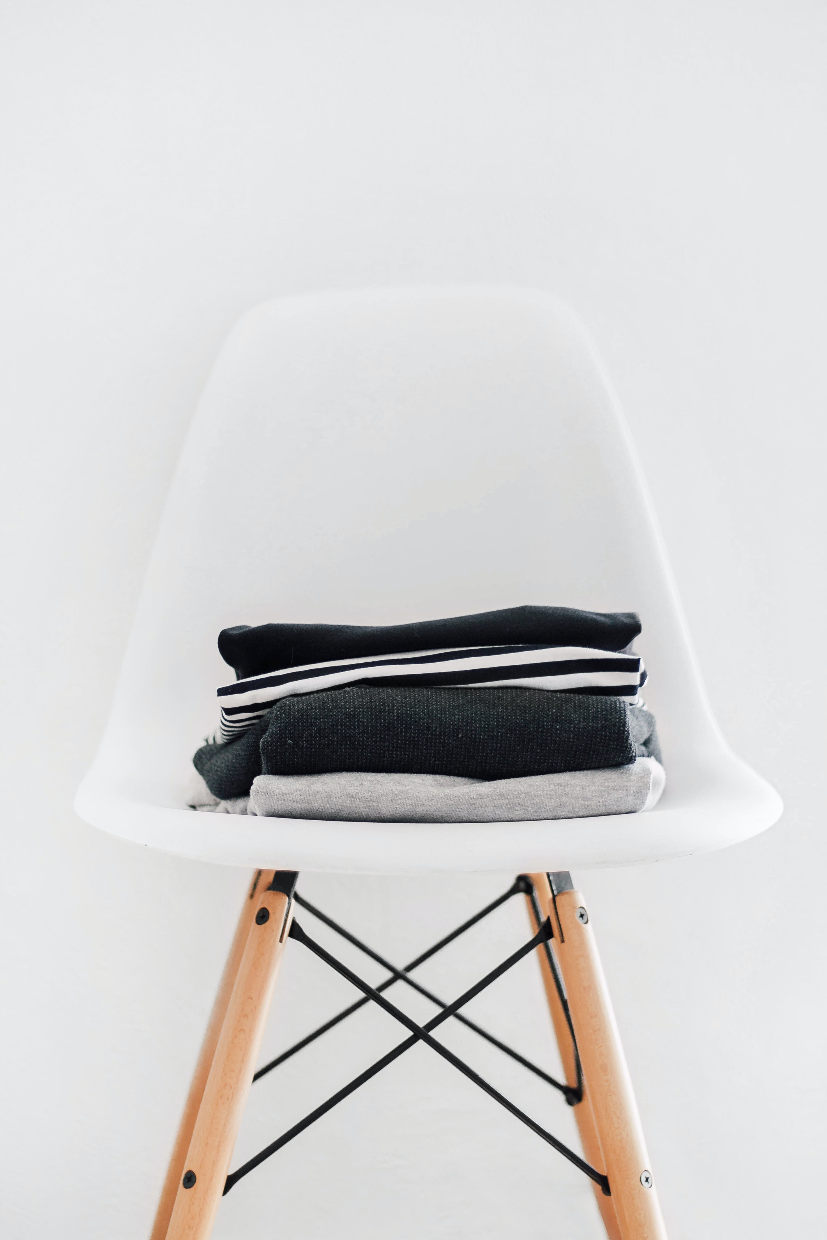Clothing sitting on top of a white chair.