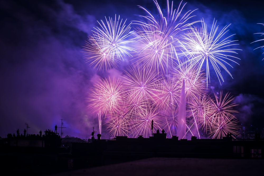 silhouette of buildings with purple and pink fireworks display