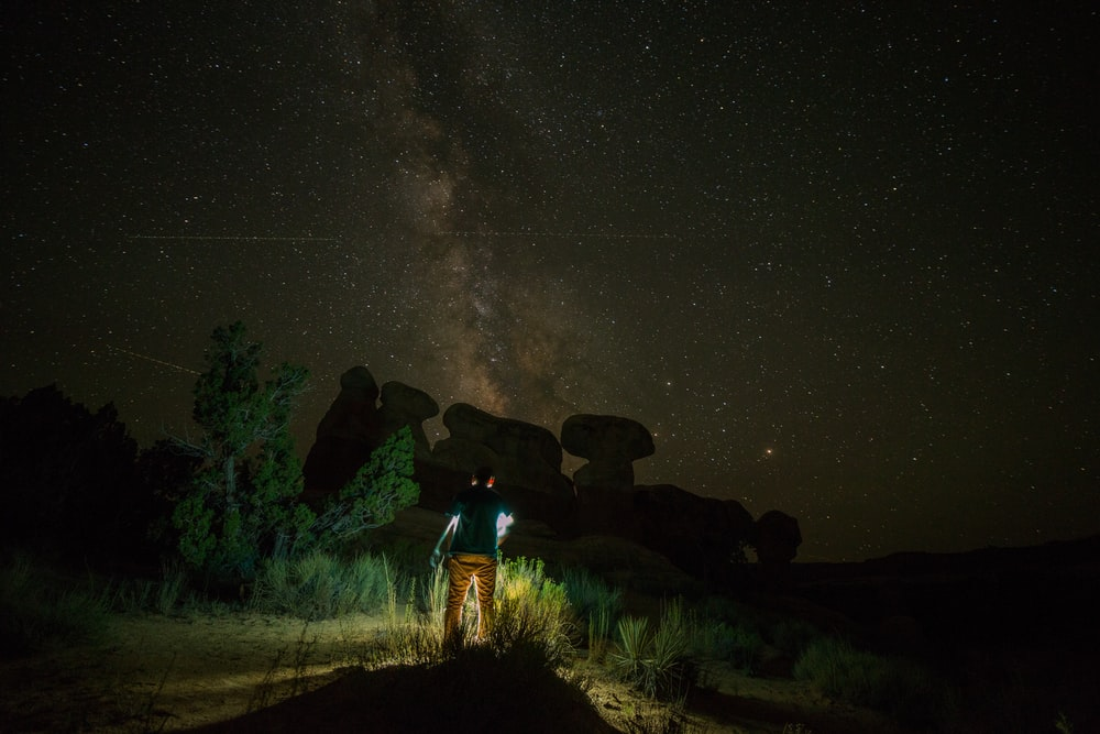 person standing near rock formation during night time