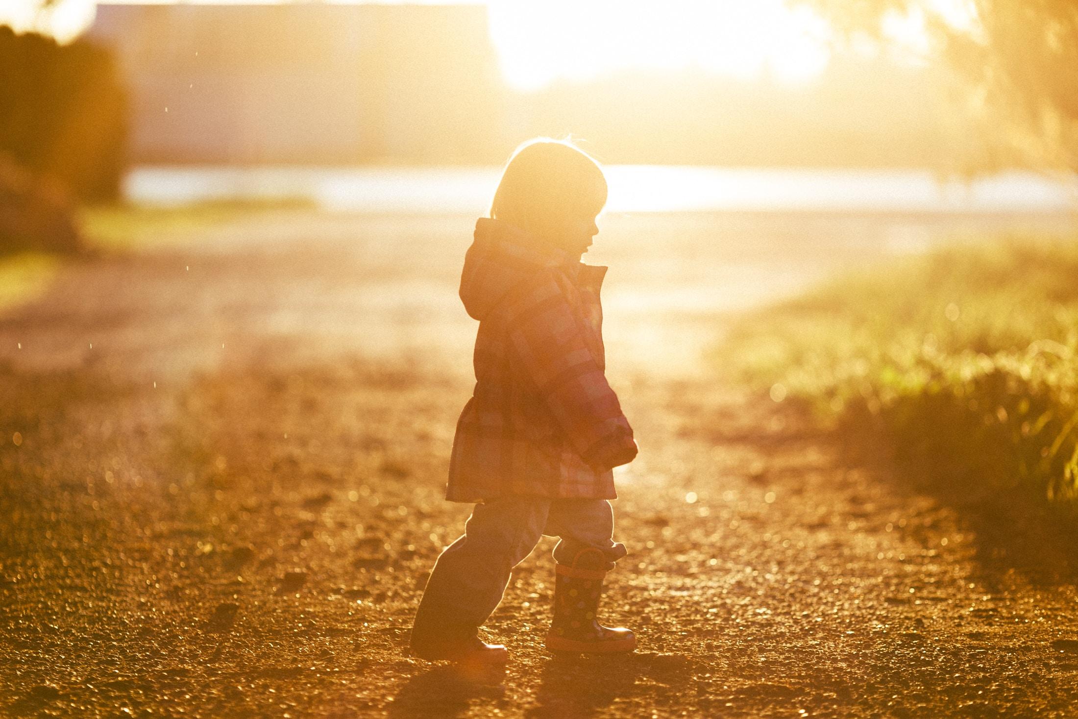 girl walking on ground towards grass