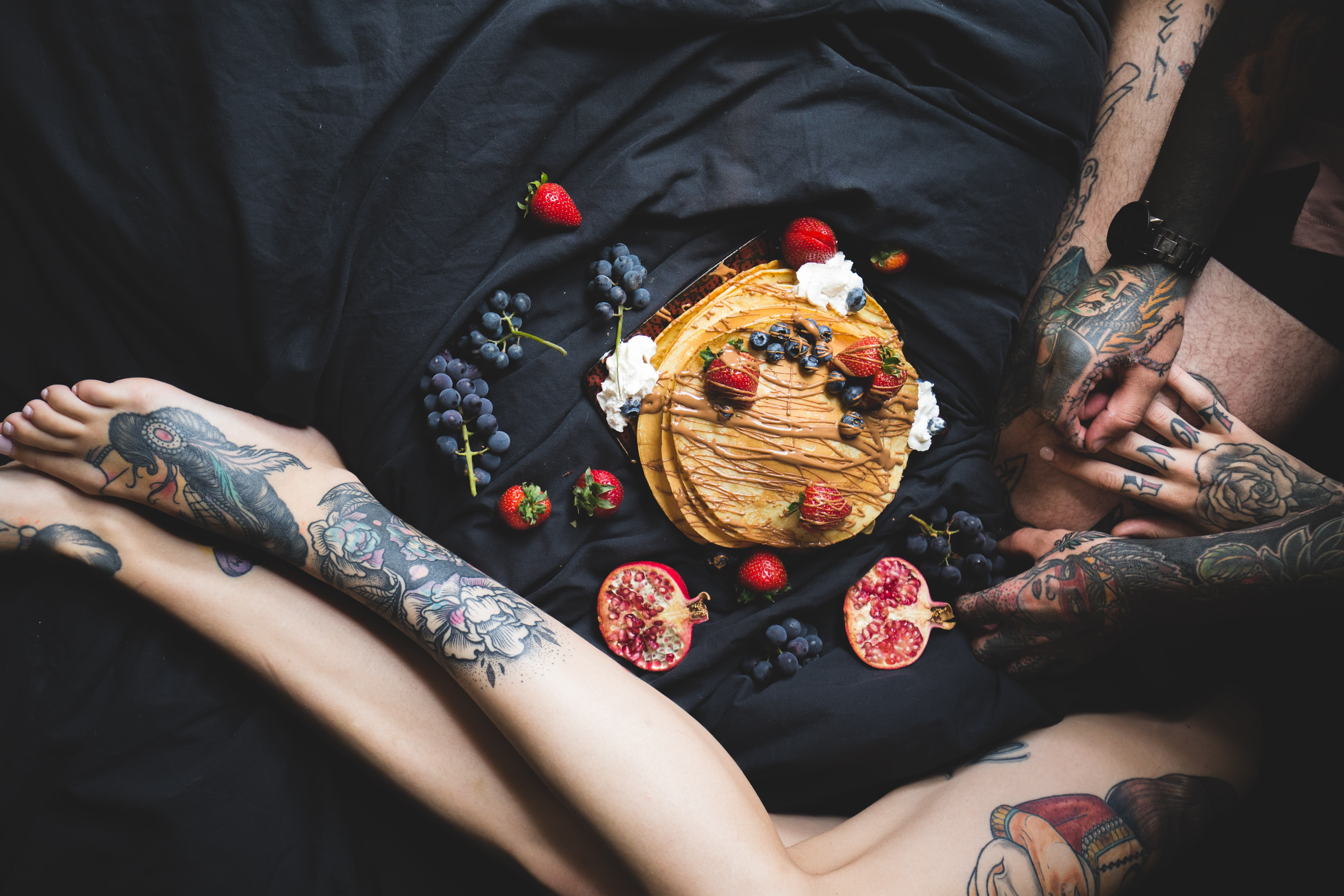 A tattooed couple lying down with pancakes and various fruits.