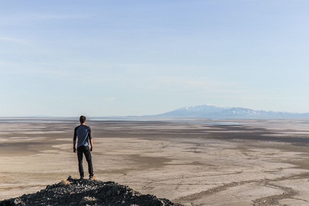 man standing on top of mountain overlooking desert during daytime