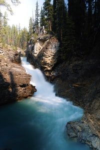 time-lapse photography of waterfalls near trees