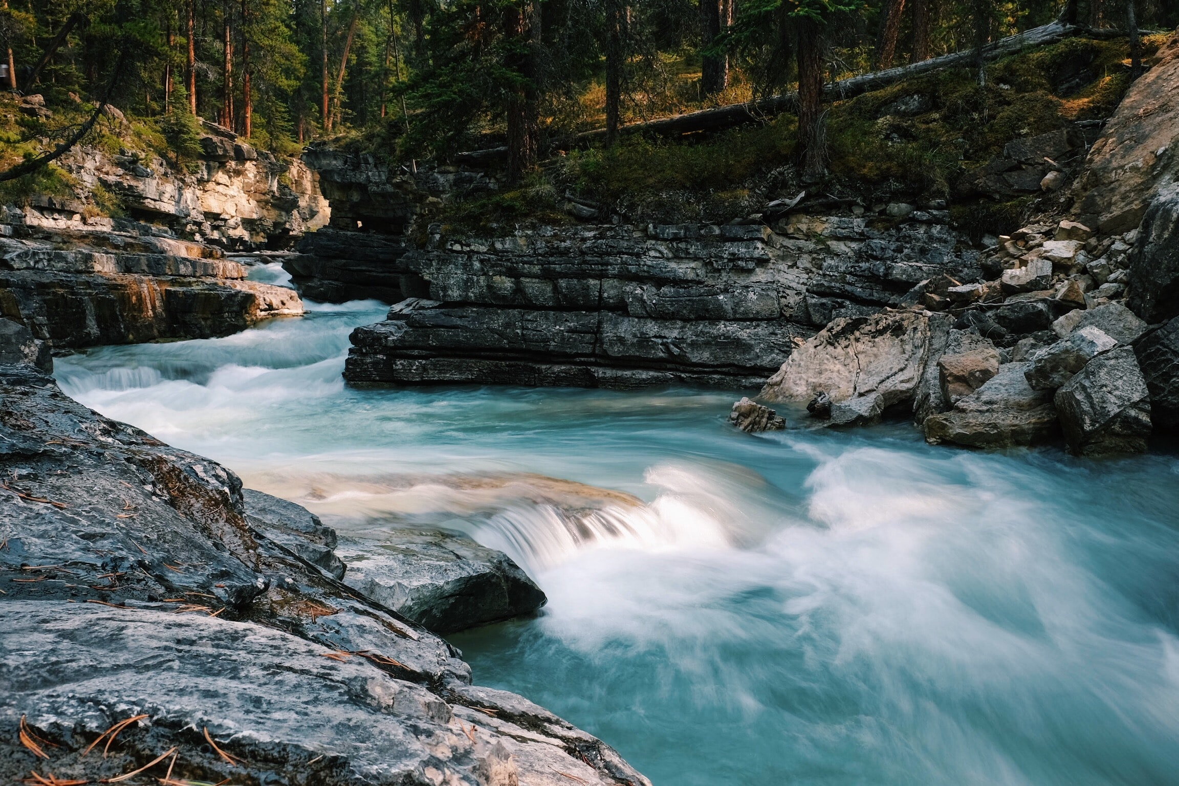 time-lapse photography of flowing river surrounded with gray rocks