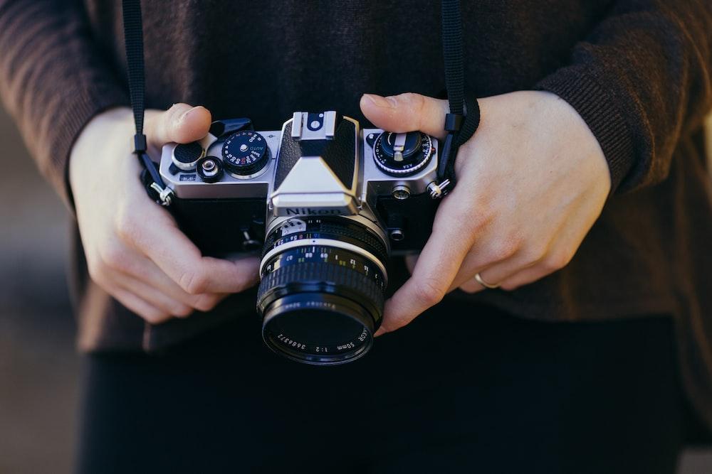 person holding gray and black SSLR camera
