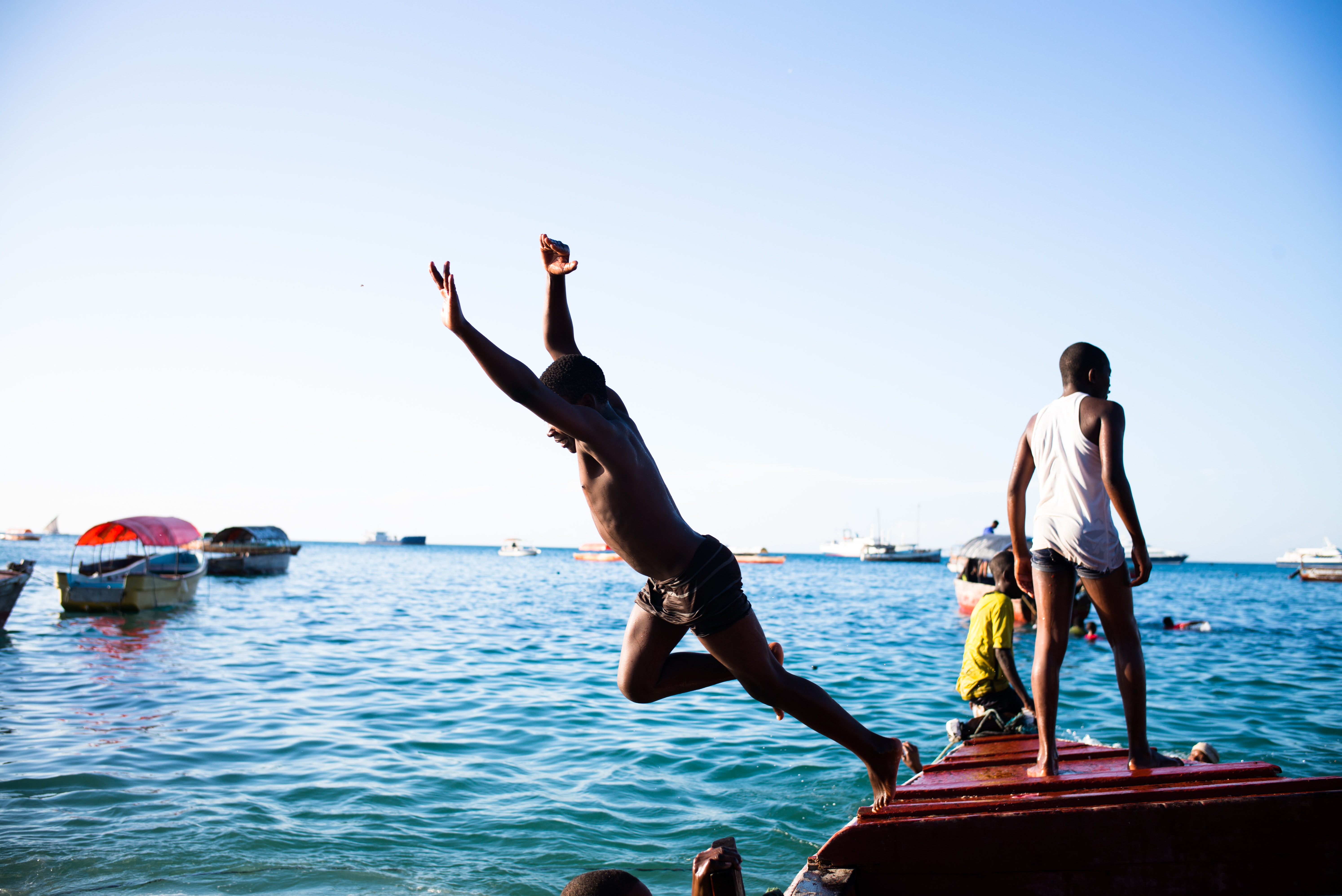 A person jumping off a dock into the water.