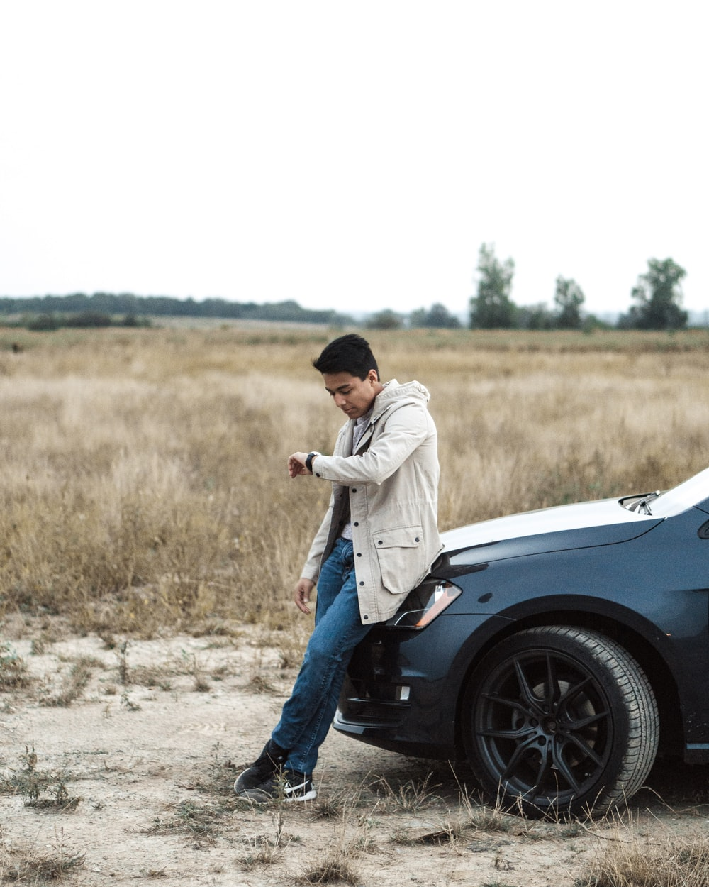 man sitting on car while looking at watch