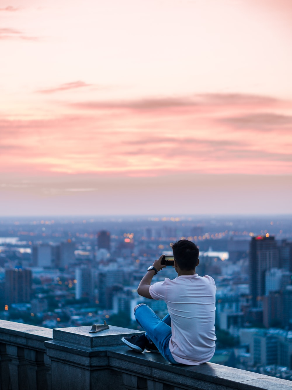 person sitting on edge of building taking photo of city during daytime