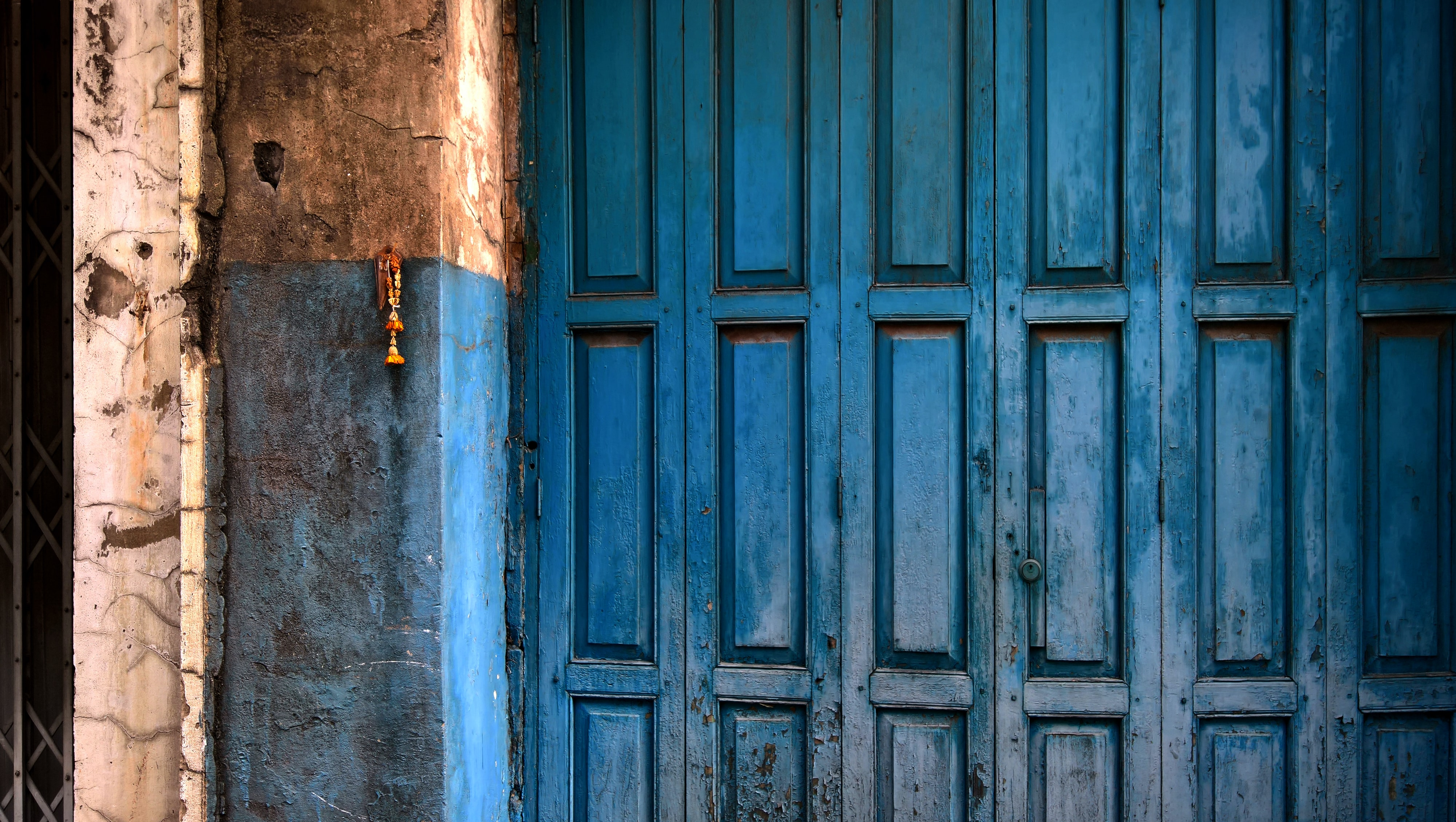 blue wooden door with panels beside blue and brown wooden concrete