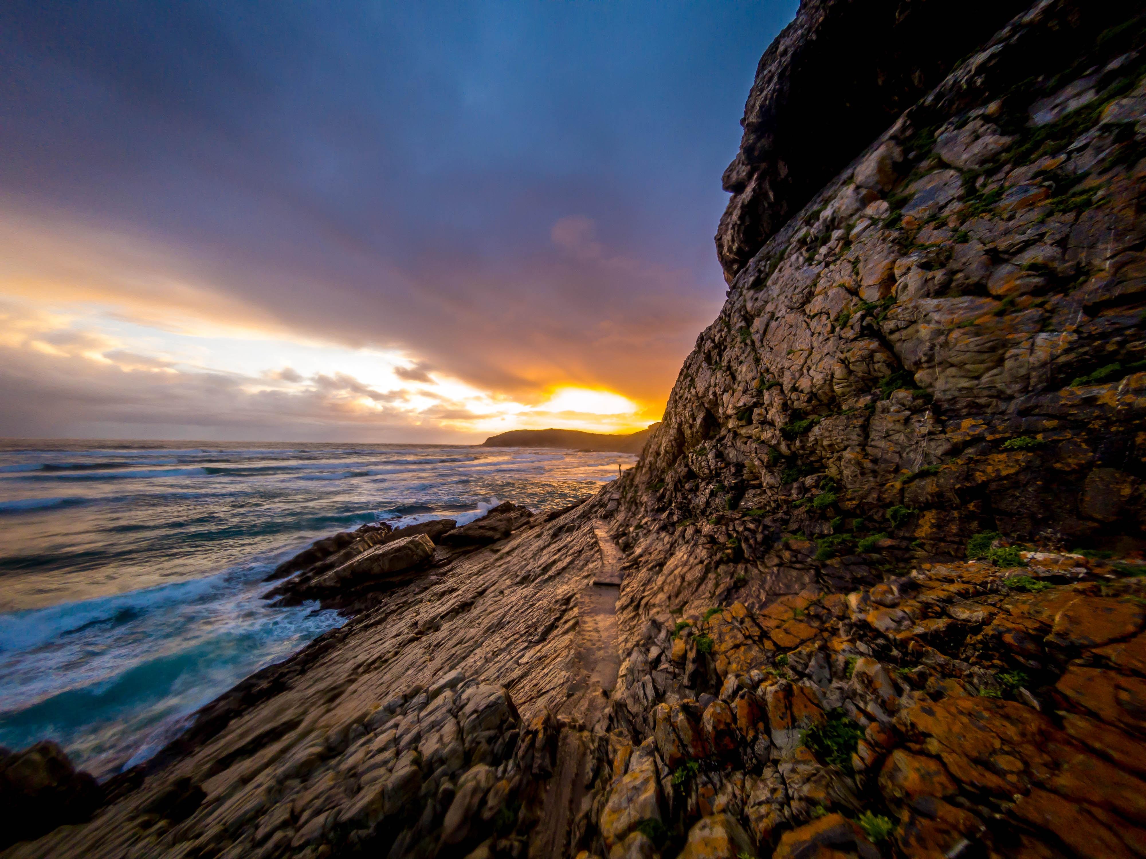 brown rock formation near seashore