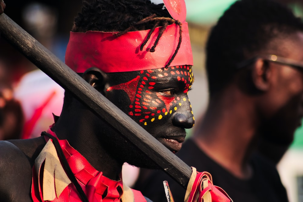 man with red and yellow face paint