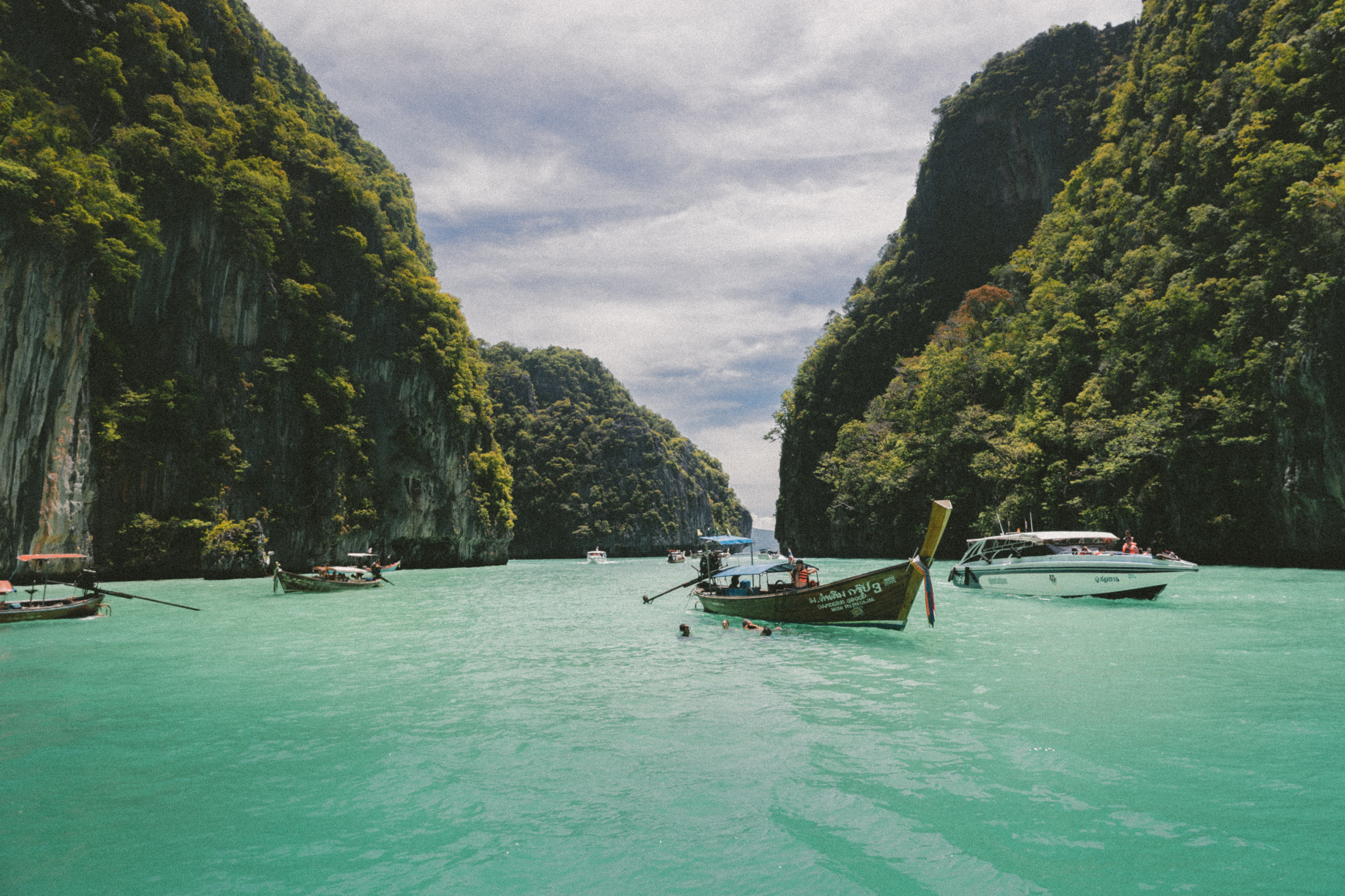 Canoes and motor powered boats driving in bluish green water under mountains.