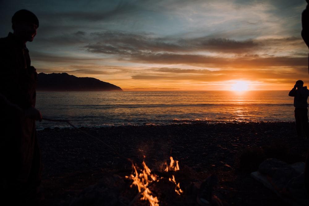 silhouette of person standing near bonfire