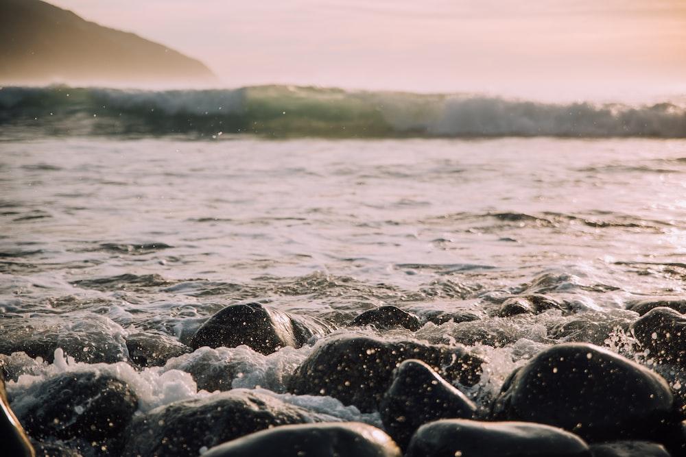 black stones near sea wave