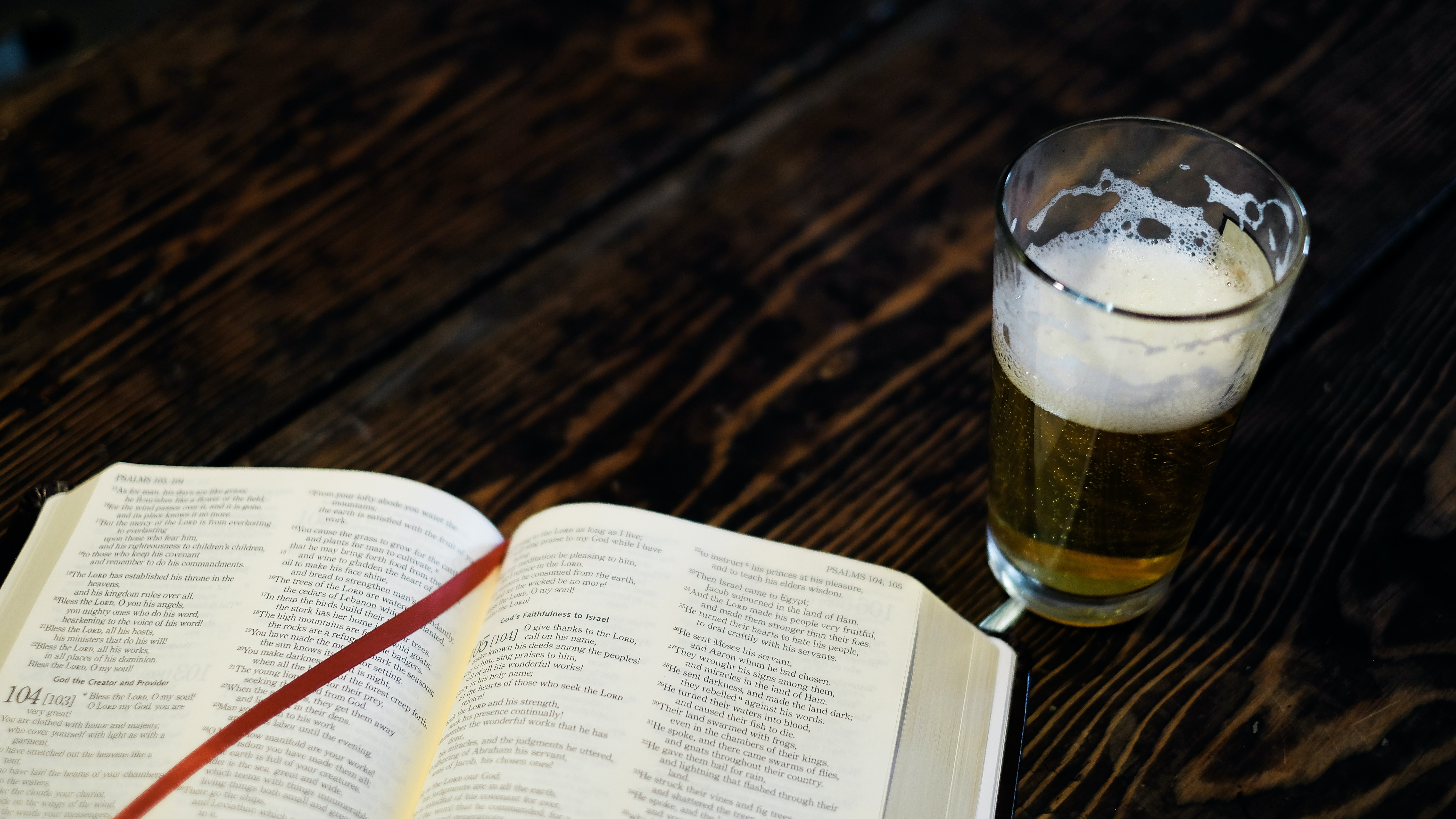 A large hardcover book next to a glass of beer.