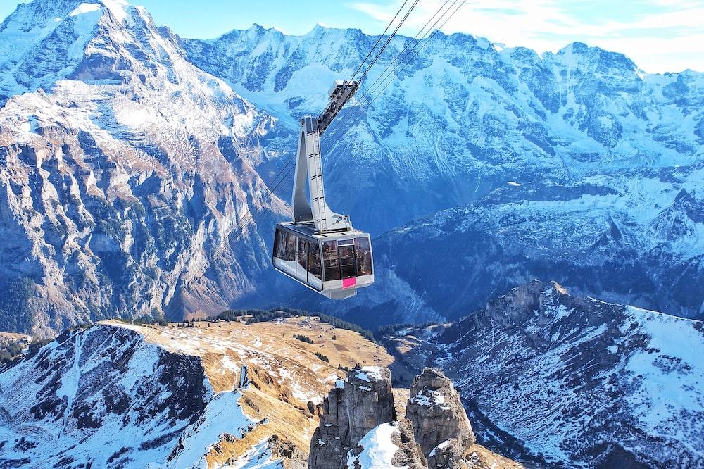 bird's eye view of ski lift over mountains during winter