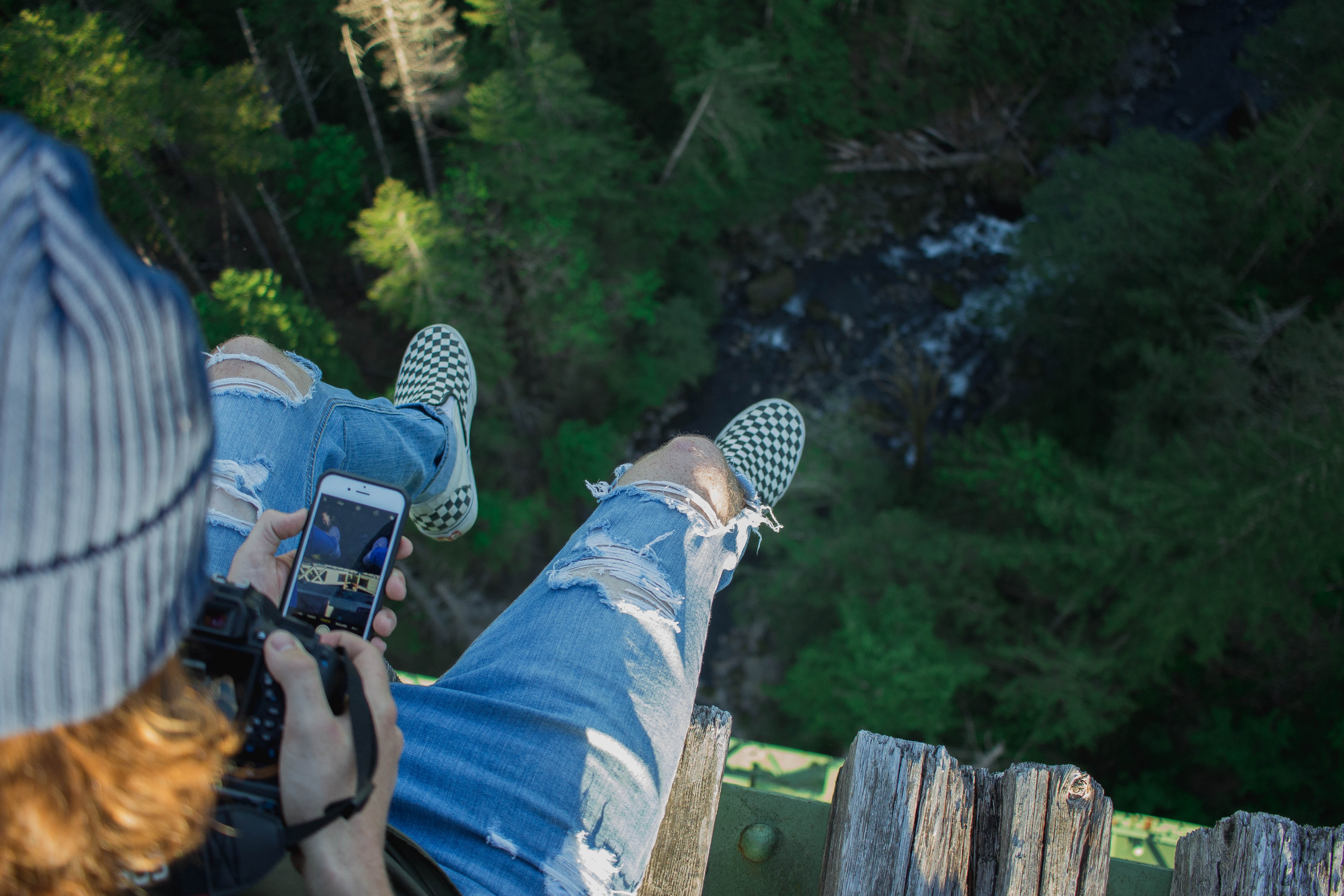 person sitting on bridge while holding phone