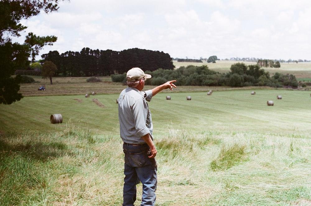 man wearing gray long-sleeved shirt on green grass field