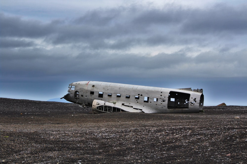 crushed plane on soil under gray sky during daytime