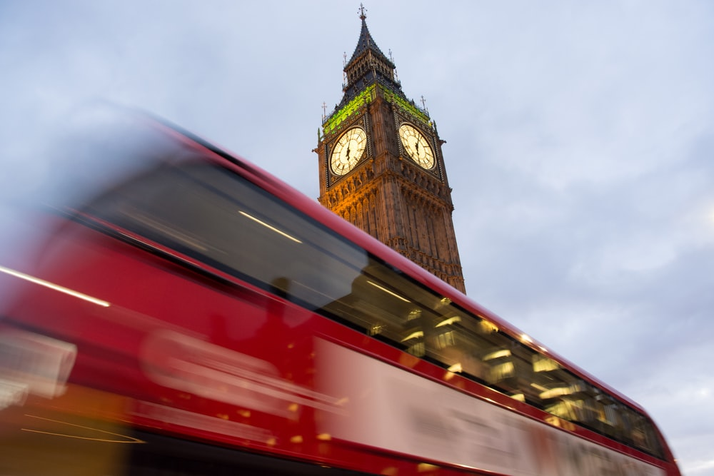 panning photography of double-decker bus passing through Elizabeth Tower