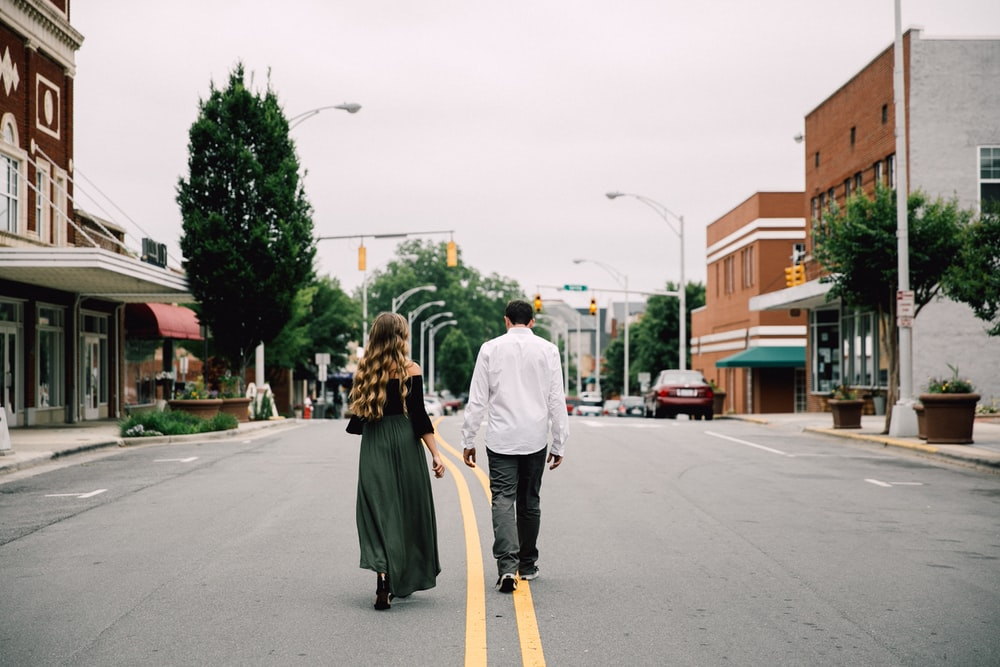 man and woman walking in the middle of the road