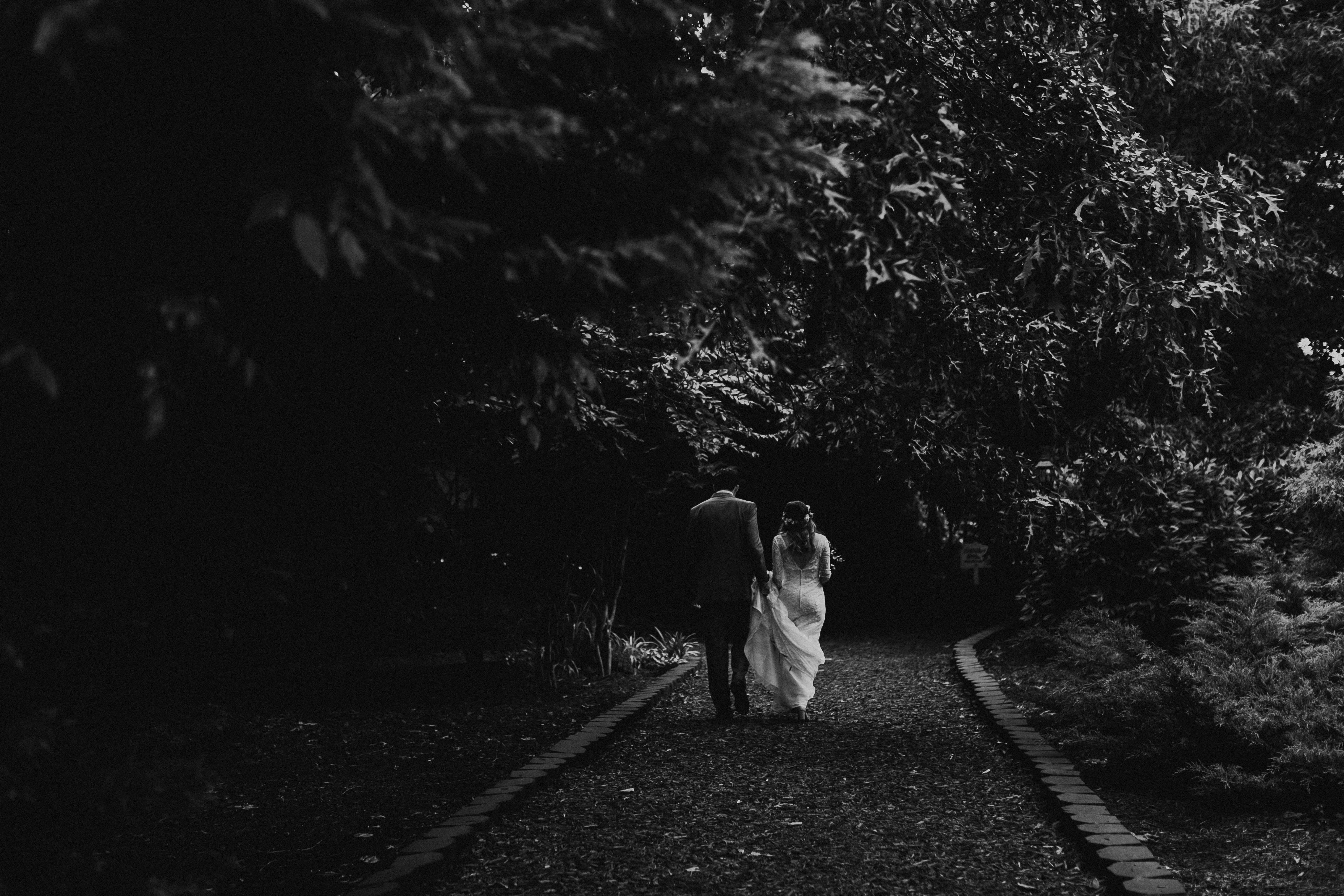 A married couple walking down a forest path.