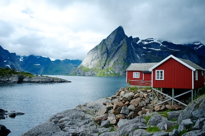 red and white wooden house in front of body of water norway teams background