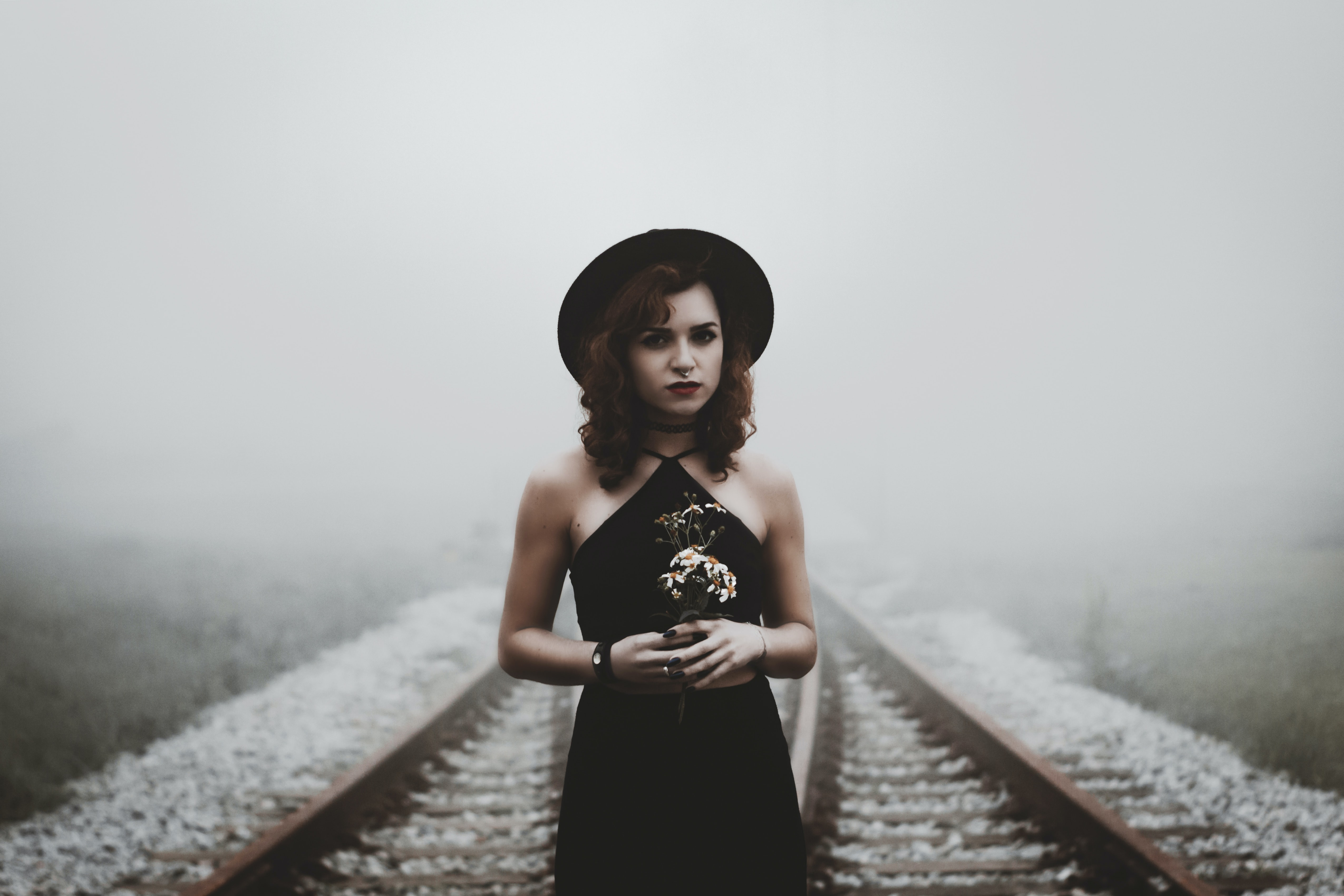woman holding her hands on railroad