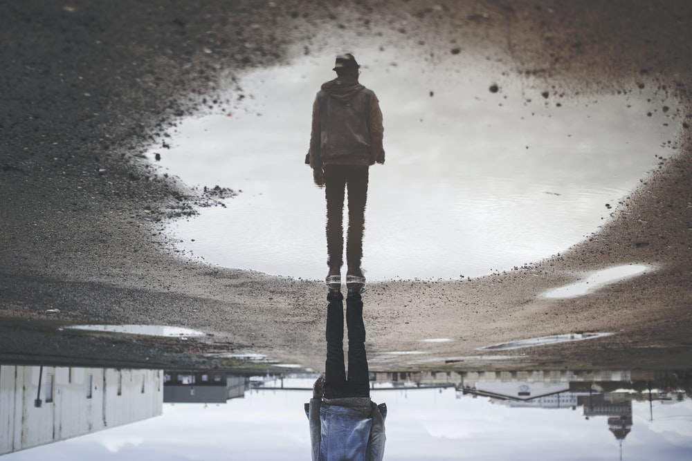 man's reflection on body of water photography
