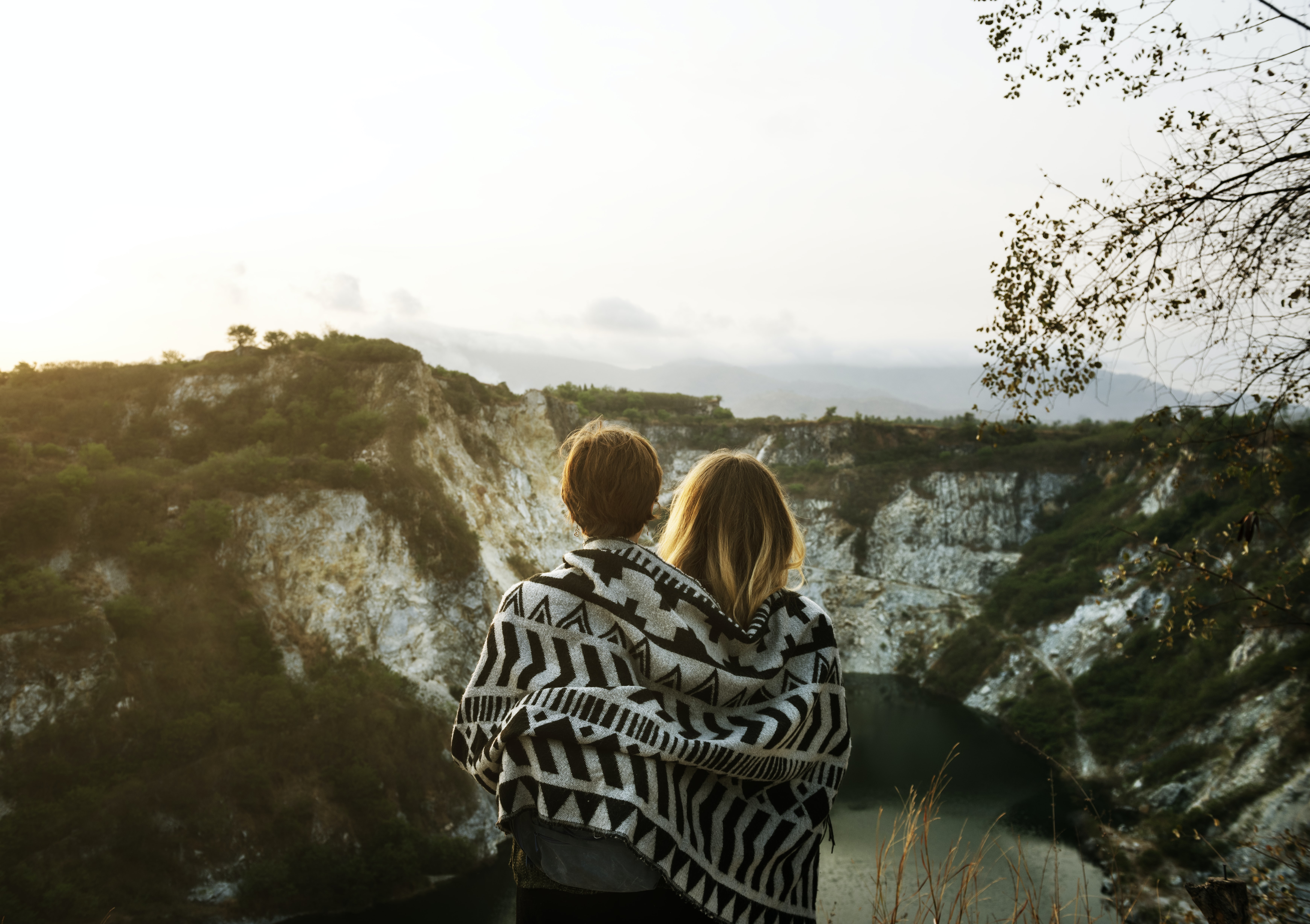 two people standing while looking on white and green mountain