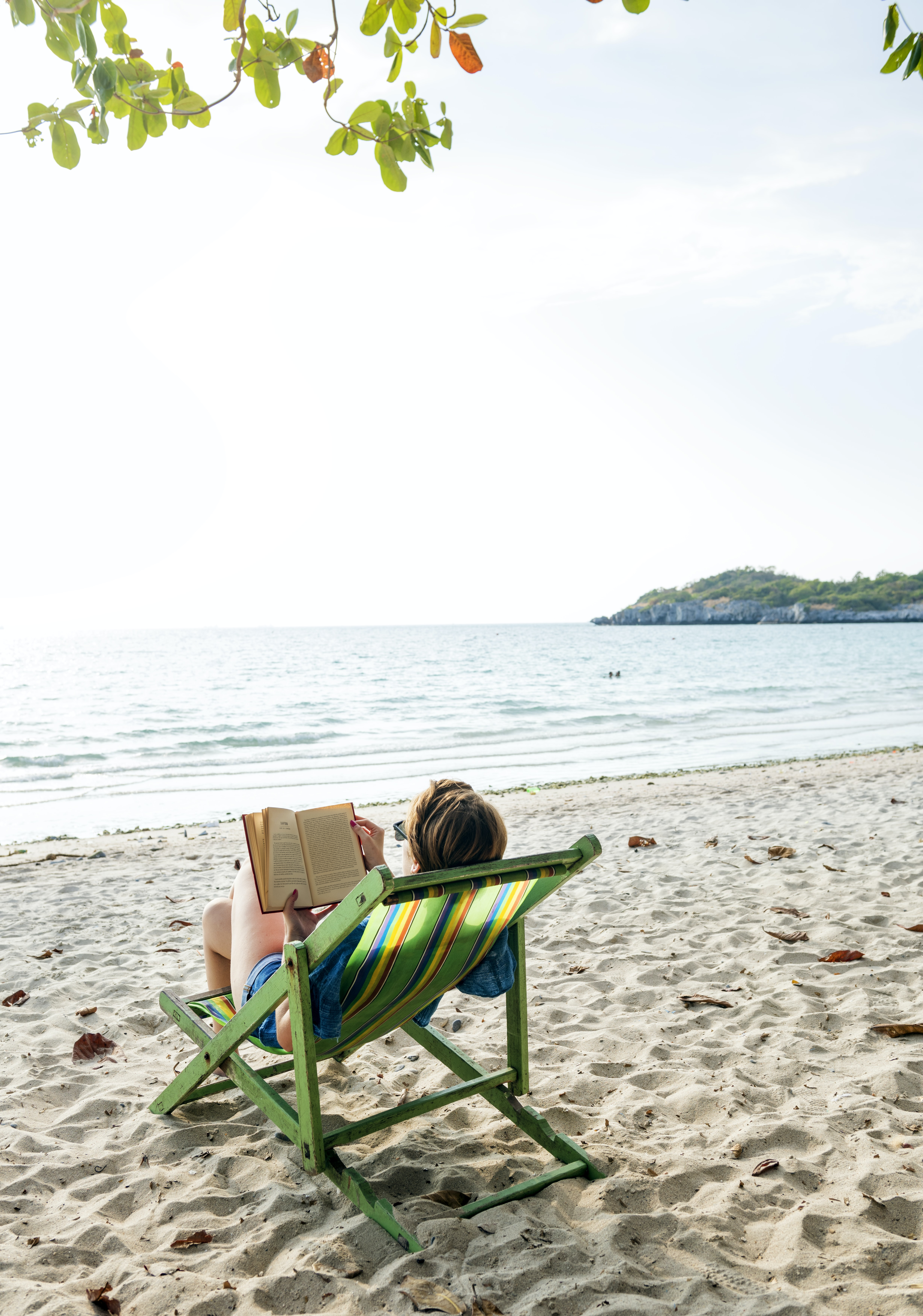person sitting on lounge chair and reading book on beach