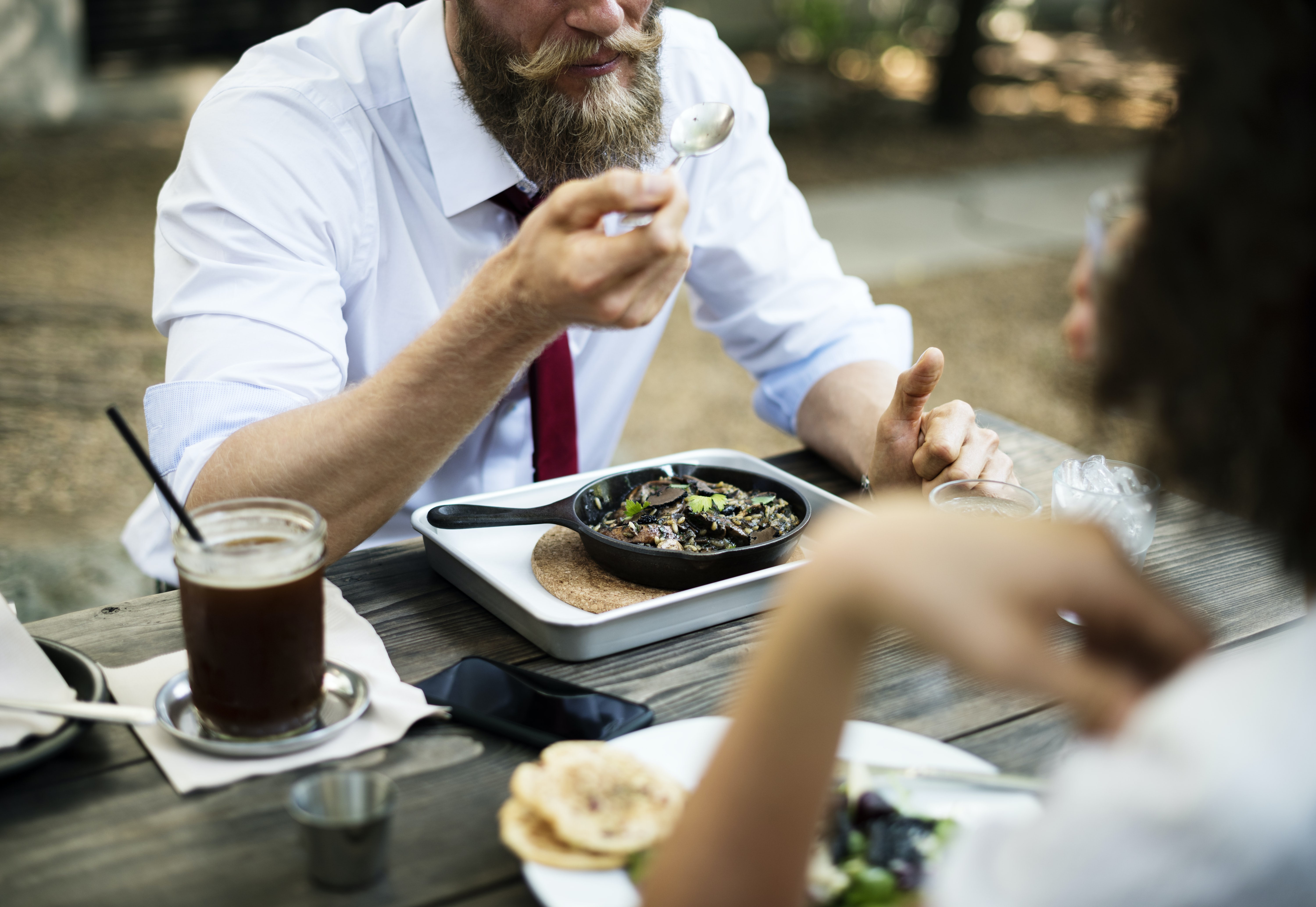 A bearded man eating lunch outside at a picnic table with a woman.