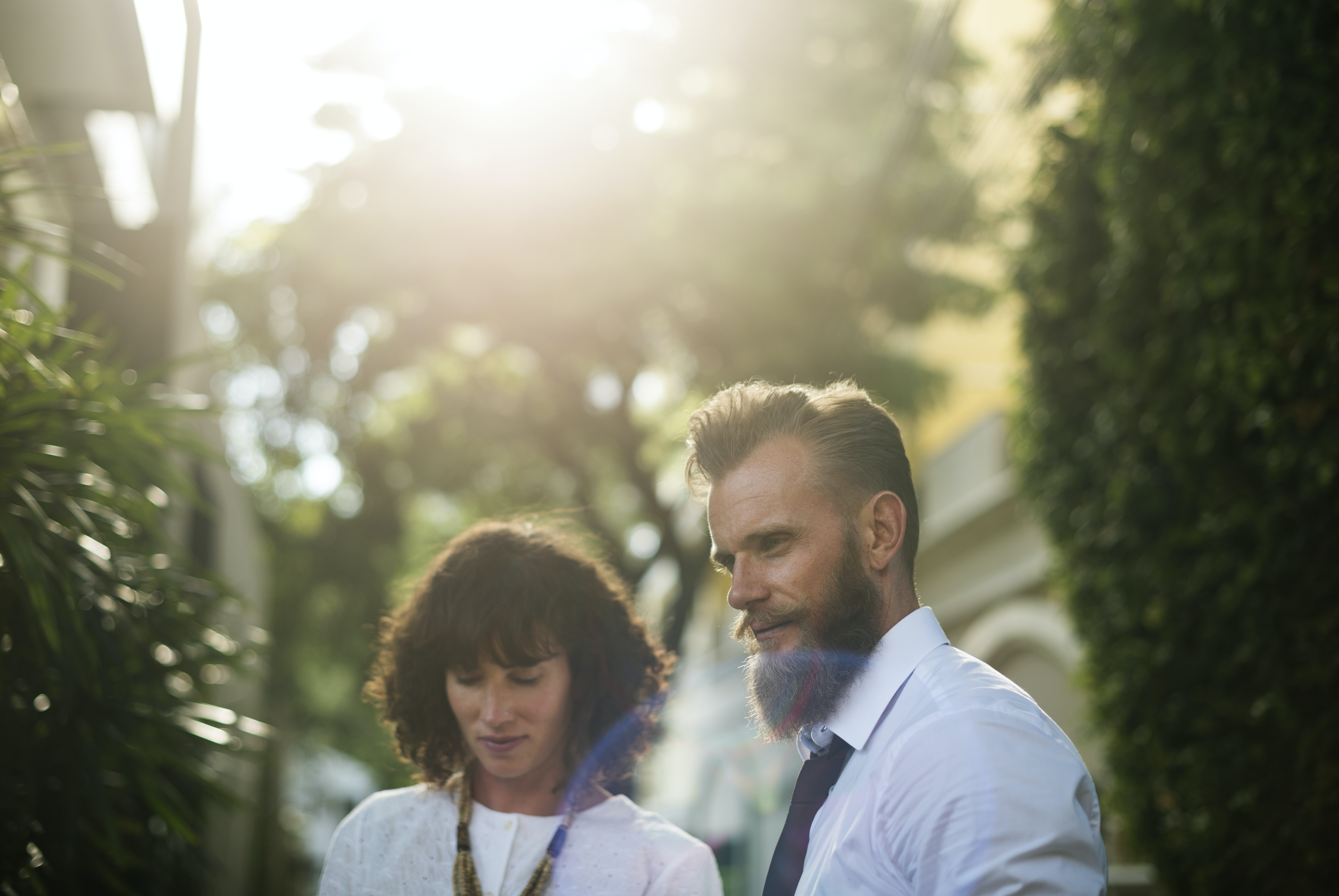 man and woman standing between green leafed plants