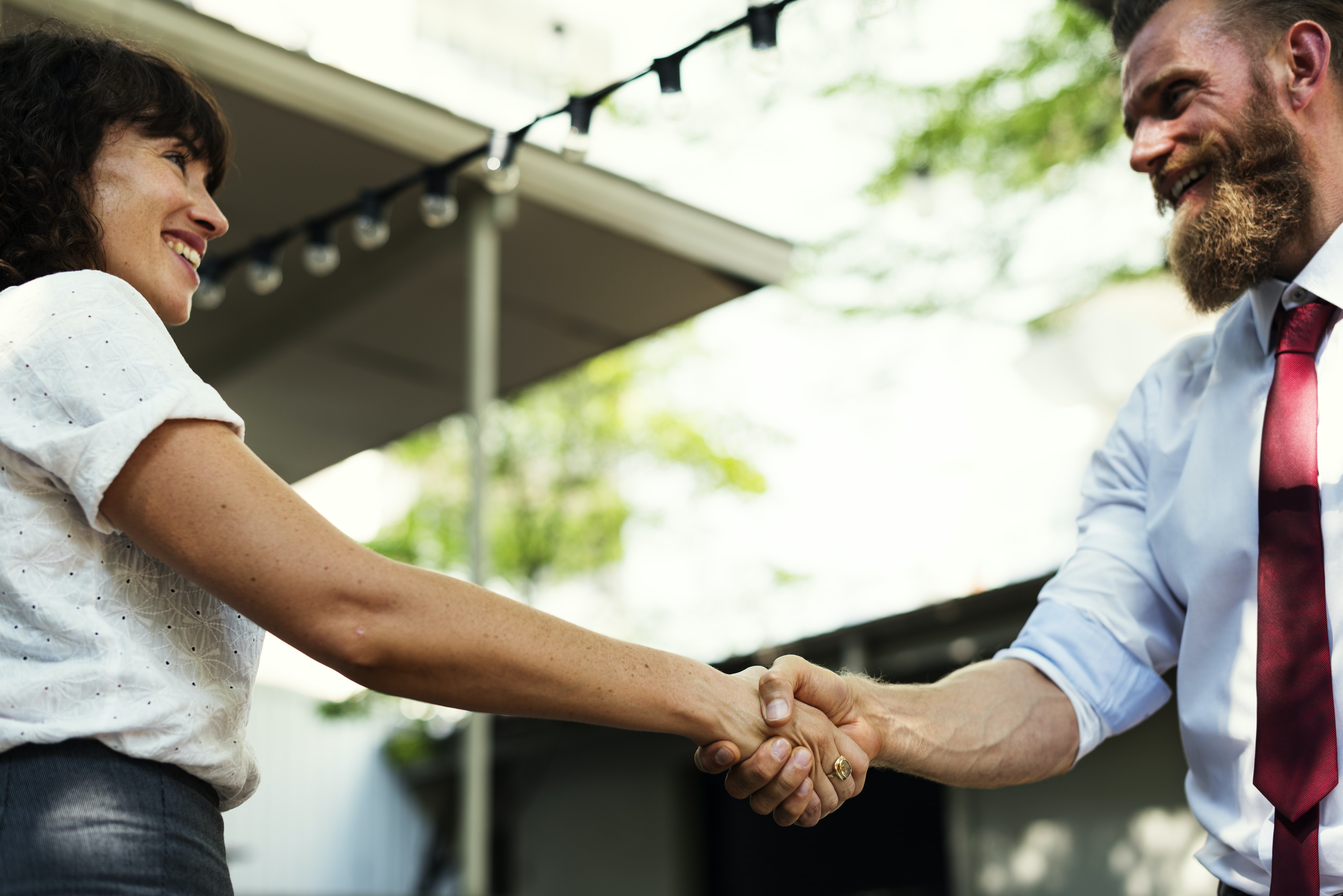 man shaking hands with woman