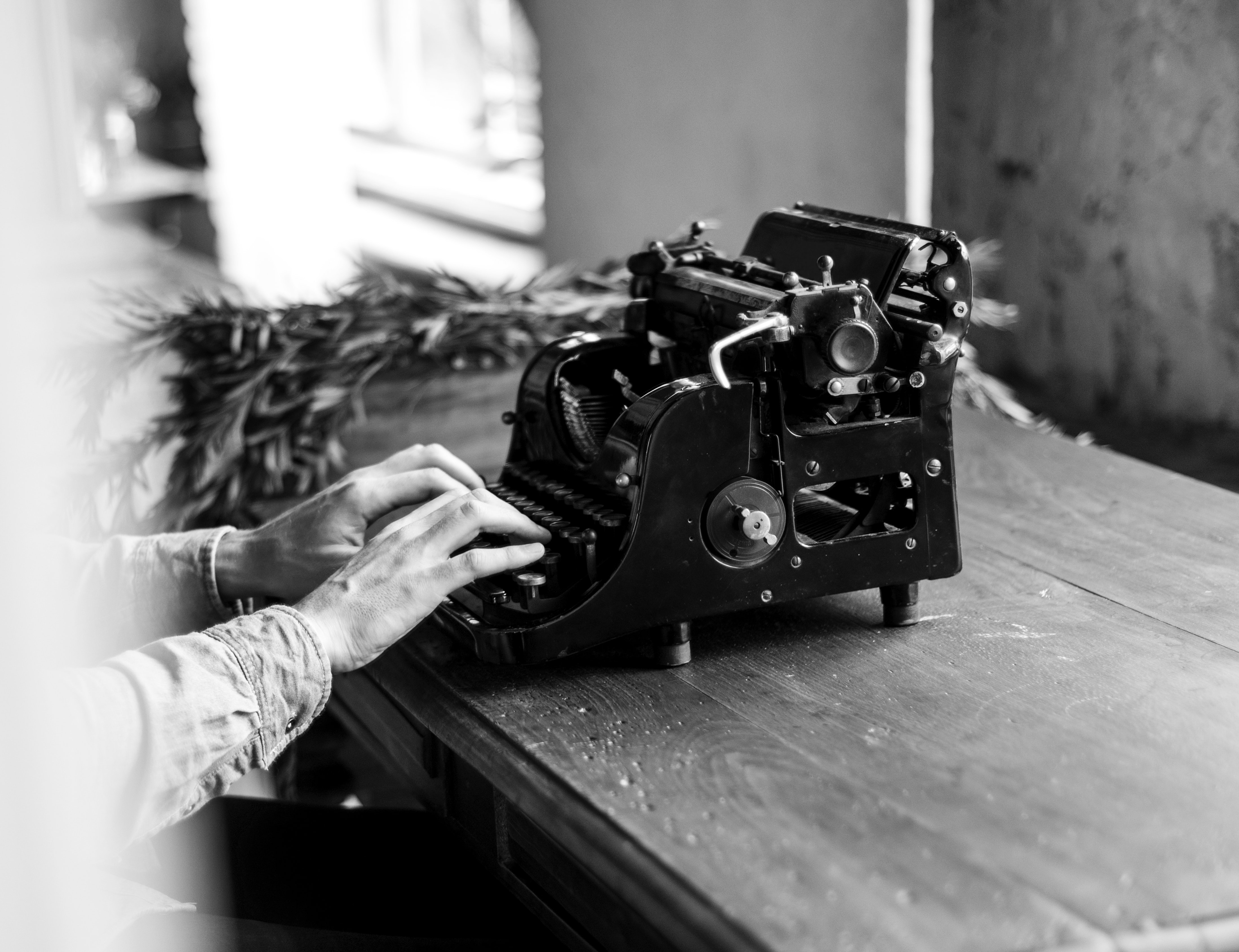 grayscale photo of person using typewriter sitting beside table