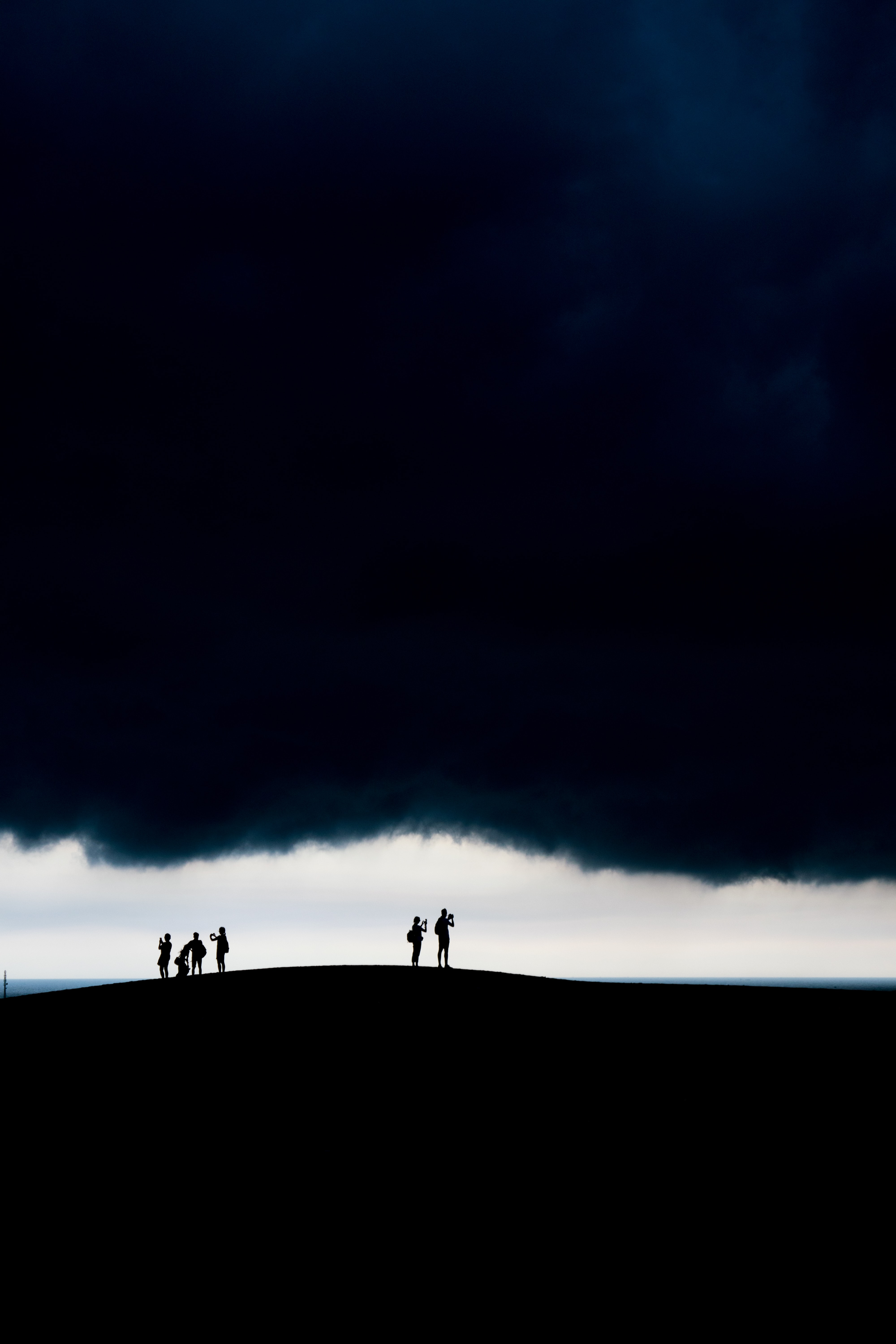 silhouette group of people on hill under dark clouds