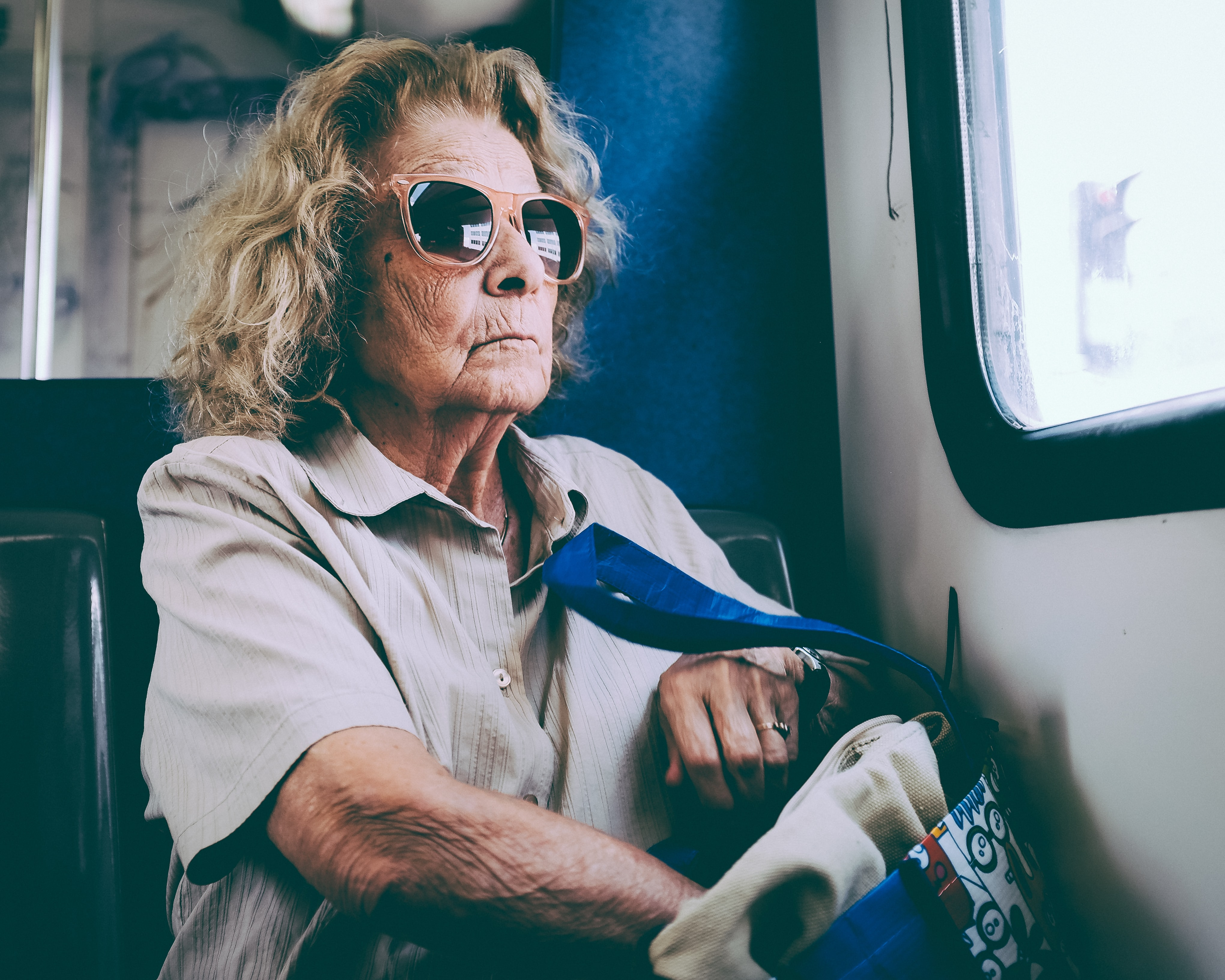 An older woman sitting on a bus.
