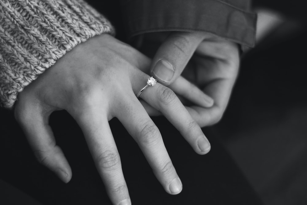 woman wearing wedding ring with man holding hand
