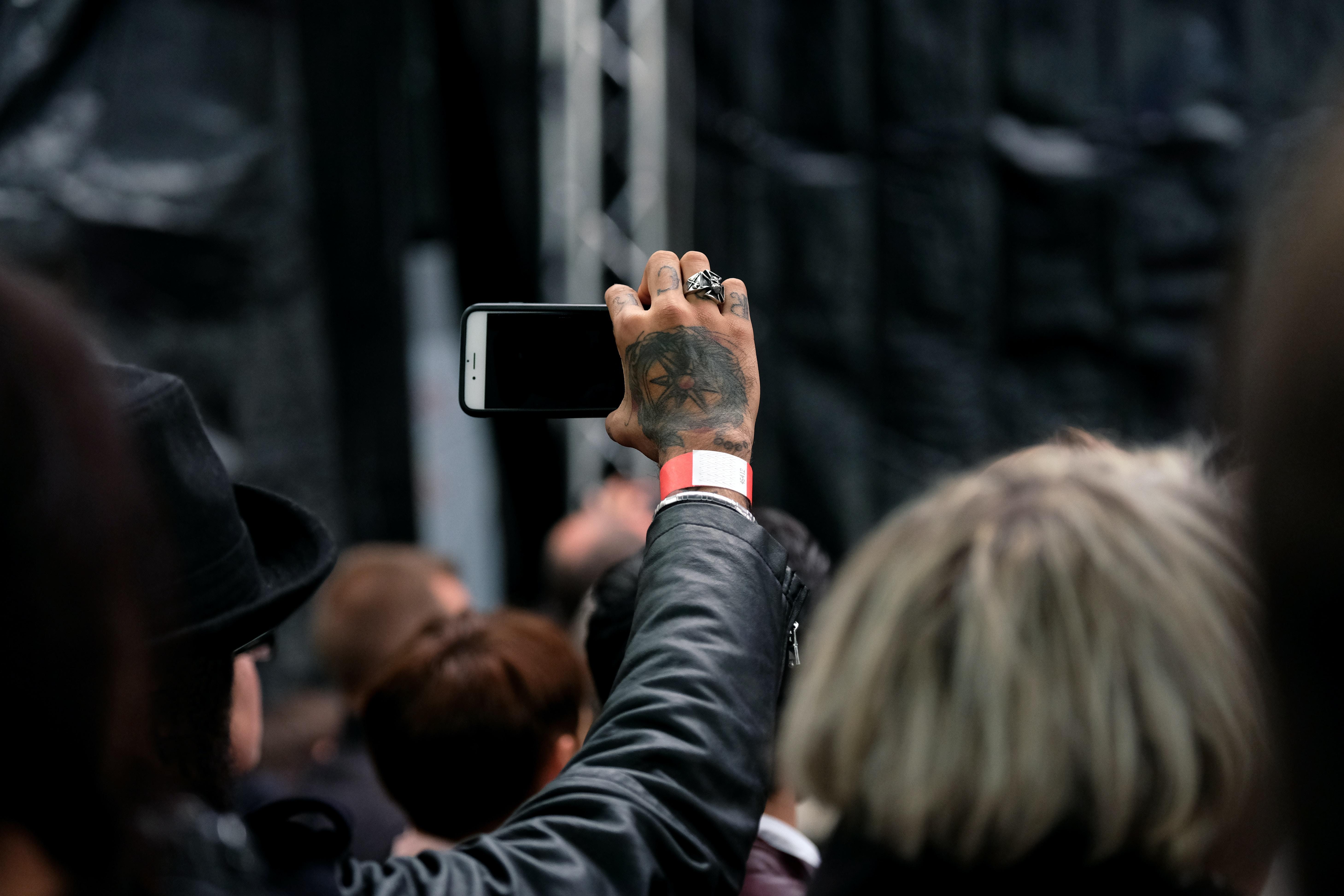 person wearing black jacket using white phone