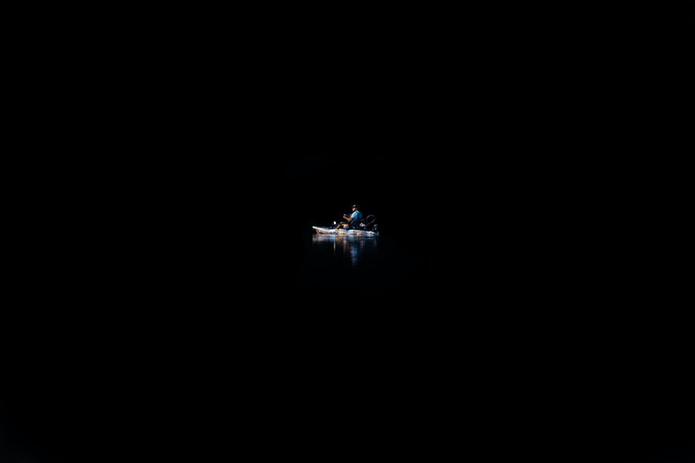 A person on a canoe in the water surrounded by complete darkness.