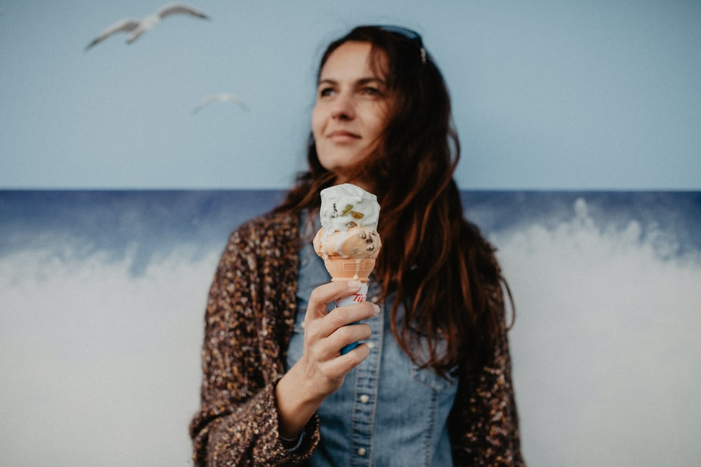 woman holding ice cream in front of wave