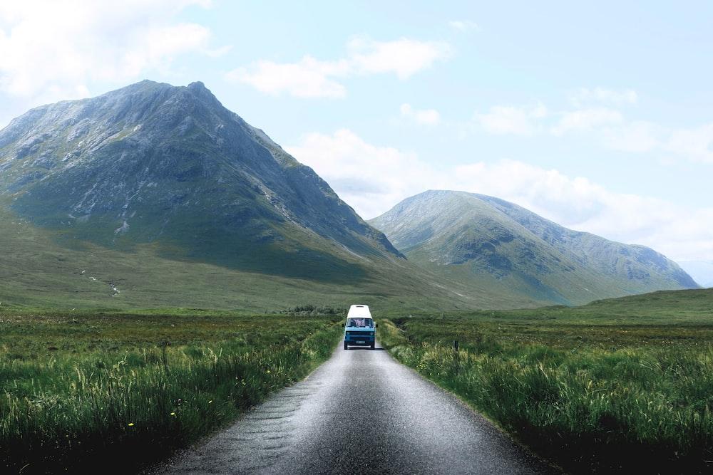 blue vehicle passing through grass field